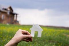 koncepcja real nieruchomości Ręka trzyma białego papieru domu postać na zamazanym zielonym tle target651_1_ ekologiczny kosmos ko Obrazy Royalty Free