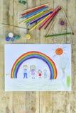 koncepcja szczęśliwa rodzina Ciąć na arkusze z wzorem na drewnianym stole: rodzice i dziecko chwyta ręki przeciw tłu tęcza i royalty ilustracja