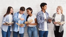 koncepcja uczenia się Nastolatkowie stoi blisko światło ściany z książkami zdjęcie royalty free