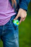 Konceptualna fotografia dziewczyny kładzenia kula ziemska w kieszeni Zdjęcia Stock