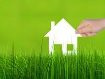Konceptualny białego papieru domu symbol trzymający w ręce w zielonej trawie Obraz Stock