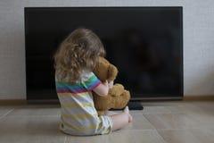 Konceptualny portret Mała dziewczynka siedzi na podłogowym obejmowaniu z pluszową zabawką na tle czarny ekran Fotografia Royalty Free