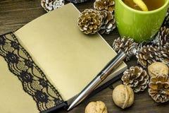 Konceptualny skład na drewnianym stole z filiżanką herbata, ręcznie robiony notatnik, jedlinowi rożki Obrazy Stock