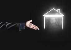 Konceptualny wizerunek z ręką wskazuje przy domowej lub głównej strony ikoną na ciemnym tle Fotografia Royalty Free