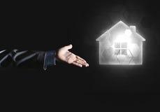 Konceptualny wizerunek z ręką wskazuje przy domowej lub głównej strony ikoną na ciemnym tle Obrazy Royalty Free