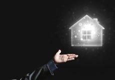 Konceptualny wizerunek z ręką wskazuje przy domowej lub głównej strony ikoną na ciemnym tle Fotografia Stock
