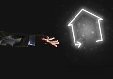 Konceptualny wizerunek z ręką wskazuje przy domowej lub głównej strony ikoną na ciemnym tle Obraz Stock
