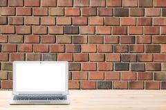 Konceptualny workspace lub biznesu pojęcie Laptop z pustym bielu ekranem na lekkim drewnianym stole przeciw czerwonemu ściana z c Obrazy Royalty Free