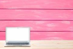 Konceptualny workspace lub biznesu pojęcie Laptop z pustym bielu ekranem na lekkim drewnianym stole przeciw malującemu różowemu w zdjęcie royalty free