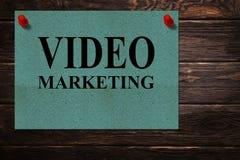 Konceptualnych wiadomości WIDEO marketing «pisać na zielonego papieru stojakach jako reklama na drewnianej powierzchni zdjęcia stock