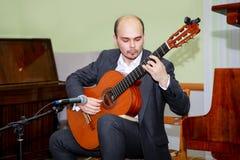 Koncertowi wykonawcy bawić się gitarę Młode gitarzysta sztuki na scenie zdjęcia royalty free