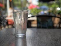Kondensation täckte exponeringsglas av vattensammanträde utanför på en mörk tabell royaltyfri foto