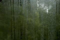 Kondensationssmå droppar i ett fönster Arkivfoto