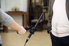 Kondensator-Schrotflinten-Mikrofon Eine Frau interviewt einen Mann Das Mikrofon in der Hand des Reporters stockbild