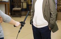 Kondensator-Schrotflinten-Mikrofon Eine Frau interviewt einen Mann Das Mikrofon in der Hand des Reporters lizenzfreie stockbilder