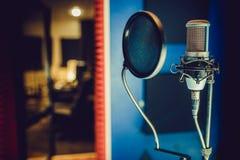 Kondensatormikrofon i en anteckna studio, popfilter royaltyfri bild