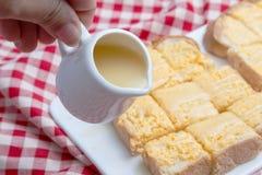 Kondenserat att hälla mjölkar på rostade bröd med smör Arkivfoton