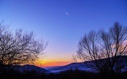 Kondensstreifen im Sonnenunterganglicht Lizenzfreie Stockbilder