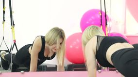 Konditionövningar i idrottshallen En gullig blondin som ligger på ett mattt pumpa en press arkivfilmer