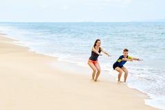 Konditionövningar Sunda par som Squatting och att öva på stranden Arkivfoton