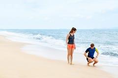 Konditionövningar Sunda par som Squatting och att öva på stranden Royaltyfria Foton