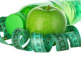 Kondition, begrepp för viktförlust med gröna äpplen, flaska av dricksvatten och måttband Royaltyfri Foto