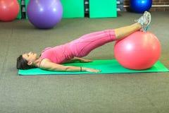 Kondition Den unga härliga vita flickan i en rosa sportdräkt gör fysiska övningar med en rosa färgpassformboll på konditionmitten royaltyfri foto