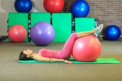Kondition Den unga härliga vita flickan i en rosa sportdräkt gör fysiska övningar med en rosa färgpassformboll på konditionmitten royaltyfria bilder