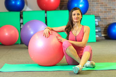 Kondition Den unga härliga vita flickan i en rosa sportdräkt gör fysiska övningar med en rosa färgpassformboll på konditionmitten arkivbilder
