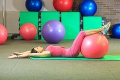 Kondition Den unga härliga vita flickan i en rosa sportdräkt gör fysiska övningar med en rosa färgpassformboll på konditionmitten royaltyfri bild