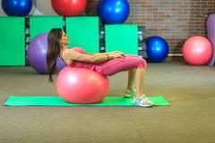 Kondition Den unga härliga vita flickan i en rosa sportdräkt gör fysiska övningar med en rosa färgpassformboll på konditionmitten arkivbild
