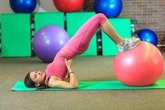 Kondition Den unga härliga vita flickan i en rosa sportdräkt gör fysiska övningar med en rosa färgpassformboll på konditionmitten arkivfoto