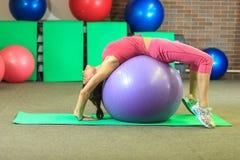Kondition Den unga härliga vita flickan i en rosa sportdräkt gör fysiska övningar med en violett passformboll på konditionmitten arkivbilder