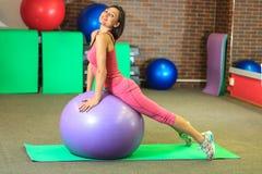 Kondition Den unga härliga vita flickan i en rosa sportdräkt gör fysiska övningar med en violett passformboll på konditionmitten arkivbild