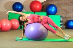 Kondition Den unga härliga vita flickan i en rosa sportdräkt gör fysiska övningar med en violett passformboll på konditionmitten arkivfoto