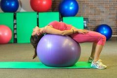 Kondition Den unga härliga vita flickan i en rosa sportdräkt gör fysiska övningar med en violett passformboll på konditionmitten royaltyfri fotografi