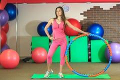 Kondition Den unga härliga vita flickan i en rosa sportdräkt gör fysiska övningar med ett beslag på konditionmitten royaltyfri foto