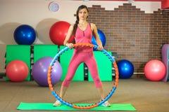 Kondition Den unga härliga vita flickan i en rosa sportdräkt gör fysiska övningar med ett beslag på konditionmitten fotografering för bildbyråer