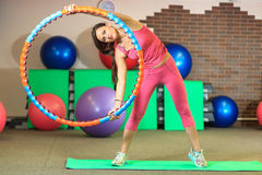 Kondition Den unga härliga vita flickan i en rosa sportdräkt gör fysiska övningar med ett beslag på konditionmitten royaltyfria foton