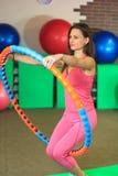 Kondition Den unga härliga vita flickan i en rosa sportdräkt gör fysiska övningar med ett beslag på konditionmitten royaltyfria bilder