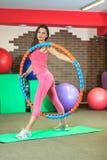 Kondition Den unga härliga vita flickan i en rosa sportdräkt gör fysiska övningar med ett beslag på konditionmitten arkivbild