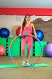 Kondition Den unga härliga vita flickan i en rosa sportdräkt gör fysiska övningar med ett beslag på konditionmitten royaltyfri bild