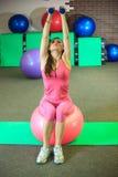 Kondition Den unga härliga vita flickan i rosa sportdräkt gör fysiska övningar med dumbells och passformbollen på konditionmitten royaltyfria foton