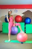 Kondition Den unga härliga vita flickan i rosa sportdräkt gör fysiska övningar med dumbells och passformbollen på konditionmitten arkivbild
