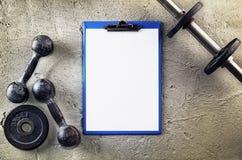 Kondition- eller bodybuildingbakgrund Gamla järnhantlar på conretegolv i idrottshallen Fotografi som tas från över, överkant royaltyfria bilder