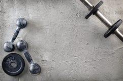 Kondition- eller bodybuildingbakgrund Gamla järnhantlar på conretegolv i idrottshallen Fotografi som tas från över, överkant Royaltyfri Fotografi
