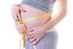 Kondition för en gravid flicka Mäta magen av en gravid kvinna royaltyfria foton