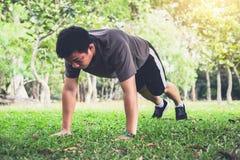 Kondition för genomkörare för manliggande armhävningövning som gör utanför på gräs in royaltyfri foto