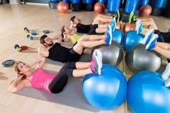 Kondition för kärna för grupp för Fitball knastrandeutbildning på idrottshallen Arkivbild