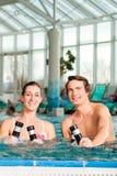 Kondition - gymnastik under vatten i simbassäng Arkivbilder